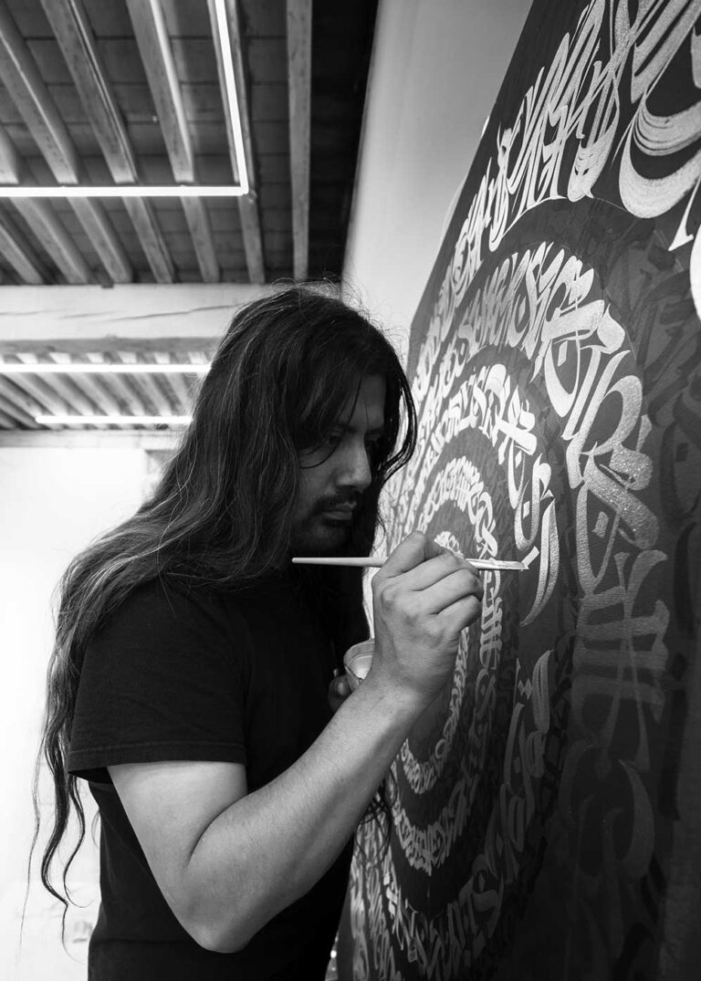 Portrait of the contemporary artist Said Dokins painting a canvas with calligraphy and calligraffiti
